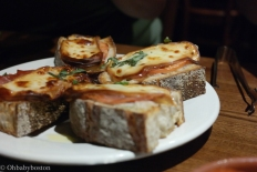 Pane at Artú. Grilled Country bread topped with smoked mozzarella, Backyard Farm Tomatoes and proscuitto.